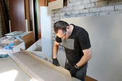Mens die met meubilair werken stock foto's