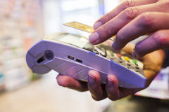 Mens die met NFC-technologie op creditcard, in apotheek betaalt stock foto