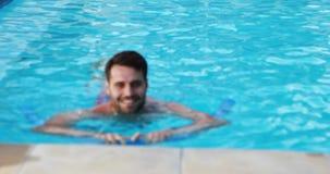 Mens die met opblaasbare buis in de pool zwemmen stock videobeelden