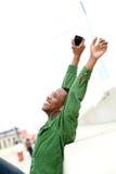 Mens die met opgeheven wapens en mobiele telefoon glimlachen Stock Foto's