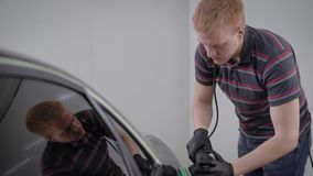 Mens die met poetsmiddel zwarte auto in de garage behandelen stock videobeelden