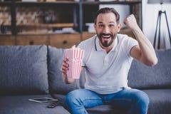 Mens die met popcorn op TV letten stock foto's