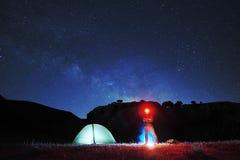 Mens die met rode koplamp dichtbij aanstekende tent in camera, op sterrige hemel als achtergrond kijken royalty-vrije stock fotografie