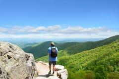 Mens die met rugzak in bergen op een reis van de de zomervakantie wandelen Royalty-vrije Stock Afbeelding