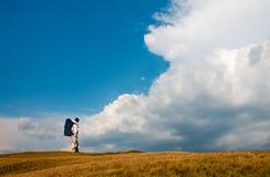 Mens die met rugzak een stormachtige hemel bekijken Stock Afbeelding