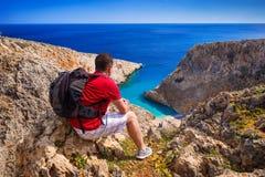 Mens die met rugzak op mooi strand op Kreta letten stock fotografie