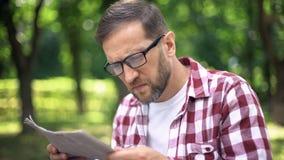 Mens die met slecht gezicht krant in park, verziendheid, bijziendheid proberen te lezen stock afbeelding