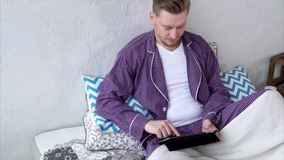 Mens die met tablet met vrienden in sociale networkson babbelen Mannetje in pyjama stock video