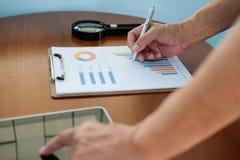 mens die met tablet op kantoor werken zakenman die grafiek D analyseren stock foto's