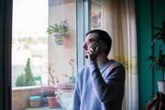 Mens die met telefoon dicht omhoog venster spreken stock foto