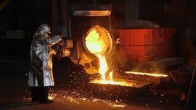 Mens die met vloeibaar metaal in fabriek werken Metaalfabriek stock video