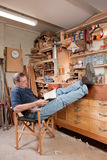 Mens die met voeten omhoog in workshop rust stock fotografie