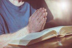 Mens die met zijn handen over de bijbel bidden stock foto's