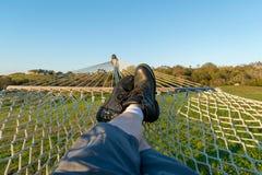 Mens die met zwarte laarzen in een hangmat, op een groen gebied op een mooie dag ontspannen stock fotografie