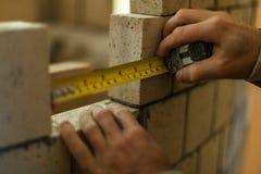 Mens die metingen maken terwijl het werken aan zijn bakstenen muur royalty-vrije stock foto