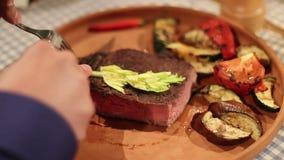 Mens die middelgroot goed lapje vlees met een mes in restaurant snijden stock video