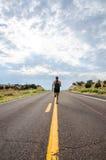Mens die in midden van verlaten woestijnweg lopen Royalty-vrije Stock Foto's