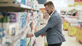 Mens die in Ministerie van huishoudengoederen winkelen in supermarkt stock videobeelden