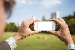 Mens die mobiele telefoon in het park met behulp van als camera royalty-vrije stock foto's