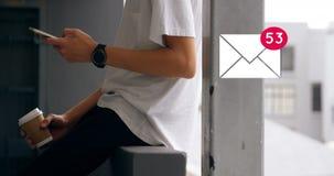 Mens die mobiele telefoon met behulp van terwijl het genieten van koffie en envelop van pictogram voor sociale media stock videobeelden