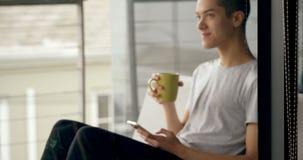 Mens die mobiele telefoon met behulp van terwijl het hebben van koffie thuis 4k stock footage