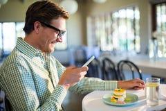 Mens die mobiele telefoon met behulp van terwijl het hebben van een lunch stock fotografie
