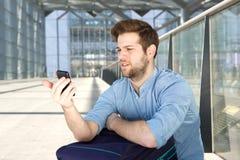 Mens die mobiele telefoon met verwarde uitdrukking bekijken royalty-vrije stock foto