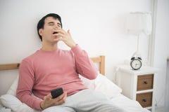 Mens die mobiele telefoon spelen Hij slaperig op bed in slaapkamer royalty-vrije stock afbeeldingen