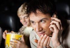 Mens die Mobilofoon in Bioskooptheater met behulp van stock afbeeldingen