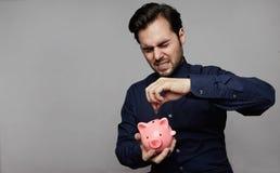 Mens die muntstuk in spaarvarken zet Het geldconcept van de besparing stock foto's