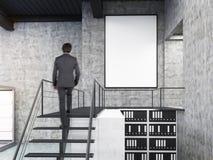 Mens die muur in bureau met treden en affiche bekijken Stock Foto's
