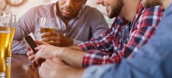 Mens die Nieuwe App op Smartphone tonen, die in Bar met Vrienden rusten stock foto's