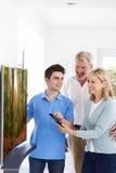 Mens die Nieuwe Televisie aantonen om Paar thuis te rijpen stock afbeelding