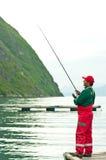 Mens die in Noorse fjord vissen stock foto's