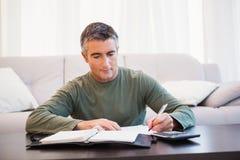 Mens die nota's met calculator en blocnote op de lijst nemen Royalty-vrije Stock Foto's