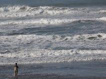 Mens die in Oceaangolven vissen Stock Fotografie