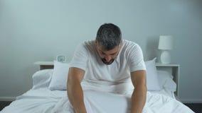 Mens die in ochtend, problemen met slaap, chronisch moeheidssyndroom proberen te ontwaken stock footage
