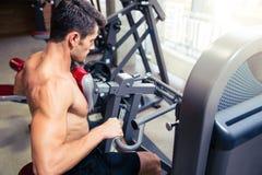 Mens die oefening op geschiktheidsmachine doen in gymnastiek Stock Foto's