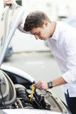 Mens die olieniveau in auto controleren Stock Afbeelding