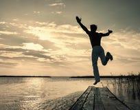 Mens die omhoog van kleine pier bij zonsondergang springen royalty-vrije stock foto's