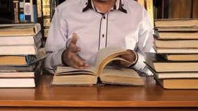 Mens die onder de boeken bestuderen stock videobeelden