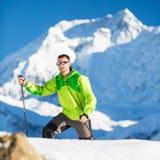 Mens die onderzoekend de winterbergen beklimmen Stock Afbeelding