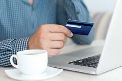 Mens die online het winkelen met creditcard op laptop doen Stock Foto