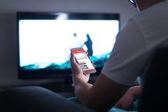 Mens die online nieuws op smartphone thuis lezen stock afbeelding