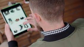 Mens die online op zijn buitensporige tablet winkelen stock video