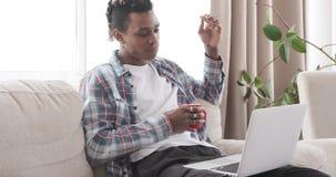 Mens die ontbijt hebben terwijl het letten op de media op laptop tevredenstellen stock video