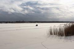 Mens die op ATV op de bevroren rivier berijden stock afbeelding