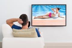 Mens die op bank het letten op televisie liggen stock afbeelding