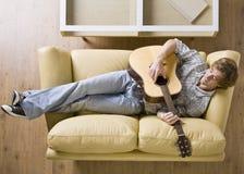 Mens die op bank het spelen gitaar legt Stock Afbeelding