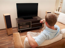Mens die op bank ligt die op TV let stock fotografie